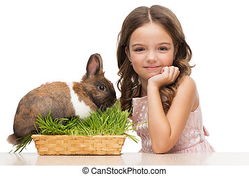Girl sitting with cute bunny and looking at camera