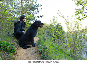Girl sitting with dog on meadow. Friendship between woman...