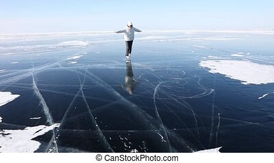 Girl skates on the transparent ice of Lake Baikal. Fun ice skating on a frozen lake on a sunny winter day.  Winter outdoor activities
