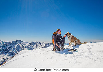 Girl ski touring with his dog at the top of the mountain