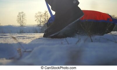 Girl sledding in winter park, young woman carries toboggan on the mountain through the sun in slow motion during beautiful sunset with amazing lense flare effects.