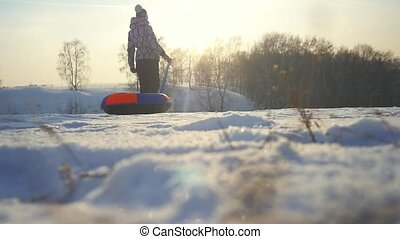 Girl sledding in winter park, young woman carries toboggan on the mountain through the sun in slow motion during beautiful sunset with amazing sun flare effect.