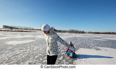 Girl sledding sister on frozen lake