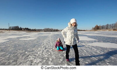 Girls sledding on plastic sled on the frozen lake. Happy girls are sledding on the frozen lake. Young girl with a sled on the frozen lake. Outdoor winter fun for family. nice winter scene. stedicam scene