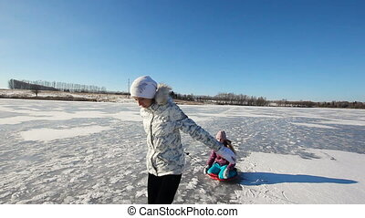 Girl sledding sister on frozen lake - Girls sledding on...