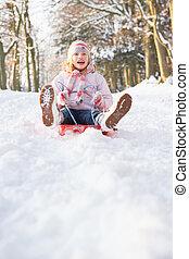 Girl Sledging Through Snowy Woodland