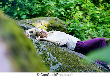 girl sleep in a forest on the rock