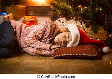 girl sleeping on floor at fireplace under Christmas tree