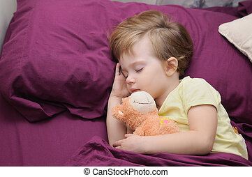 girl sleeping peacefully with her teddy bear on the bed