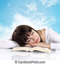 girl sleeping with a book on background sky with clouds