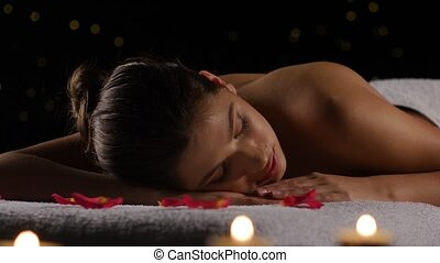 Girl sleeps after spa treatments on rose petals, burning...