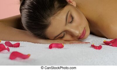 Girl sleeps after spa treatments on towels with rose petals,...