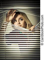 Girl slides apart jalousie. Looking outside the shot.
