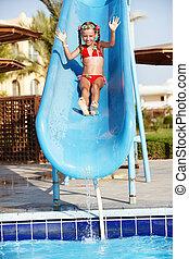Girl sliding down water slide. Summer.
