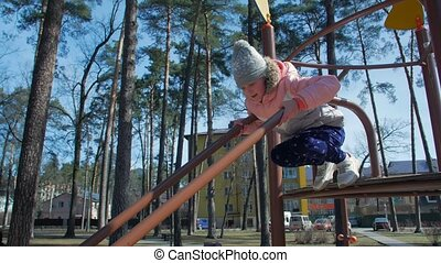 Girl sliding on the playground in the park
