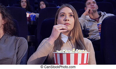 Girl slowly puts the popcorn in her mouth at the movie theater