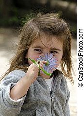 Girl smell flower - Little girl smell purple flower (Daisy)...