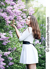 Girl smelling a lilac