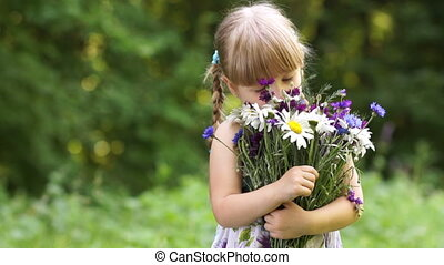 Girl smelling flower in the open sp