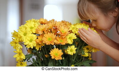Girl smells and touches yellow flowers