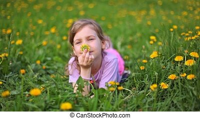 Girl smells dandelion on green lawn covered with flowers