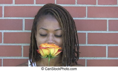 A pretty girl smiles as she smells a rose.