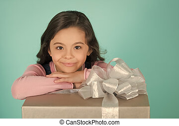 Girl smile with gift box, ribbon bow on blue background
