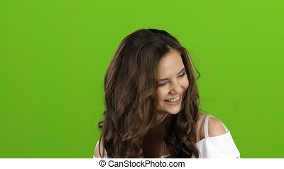 Girl smiles and gives her tenderness to everyone around her. Green screen. Close up