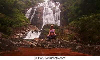 Girl Smiles in Yoga Pose by Small Lake against Waterfall -...