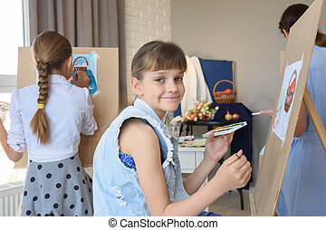 Girl smiles sitting at easel with paints in the studio