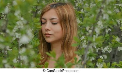 girl smiling and posing among blossoming plum - young blonde...