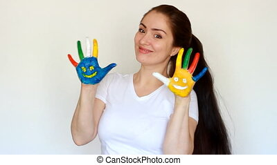 Girl smiling and showing painted dirty hands with smiles. The concept of happiness, good mood and joy