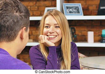 Girl smiling at the guy sitting in a cafe. The first meeting date.