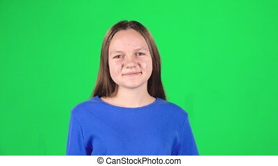 Girl smiling looking at camera on green background. Slow motion