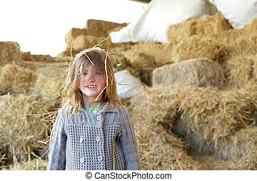 Girl smiling on a farm with hay in hair