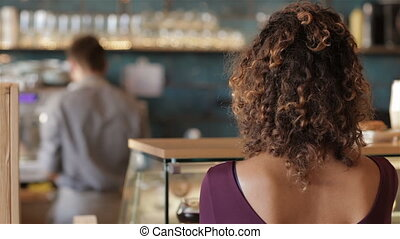 Girl smiling on the background of male barista