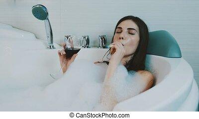 Girl smoke electronic cigarette in bath full of foam. Drink red wine. Relaxing