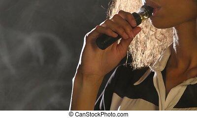 Girl smokes a vape, she enjoys a delicious aroma. Black background. Close up