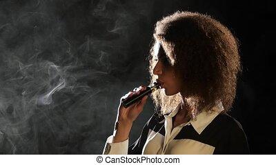Girl smokes a vape, she enjoys a delicious aroma. Black background