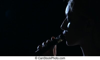 Girl smokes an electronic cigarette. Black background. Close up. Silhouette