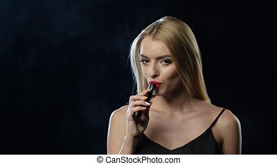 Girl smokes an electronic cigarette in a dark room. Black background