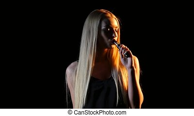 Girl smokes an electronic cigarette in an empty room. Black...