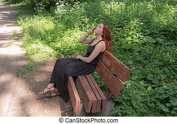 girl smokes on a bench