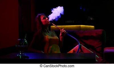 girl smoking shisha lying on sofa in cafe. Slow motion....