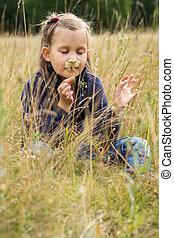 Girl sniffs a flower