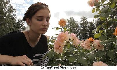 Girl sniffs roses from rose bush