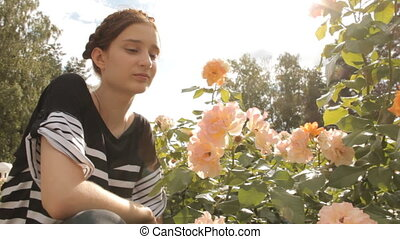 Girl sniffs roses with lens flare