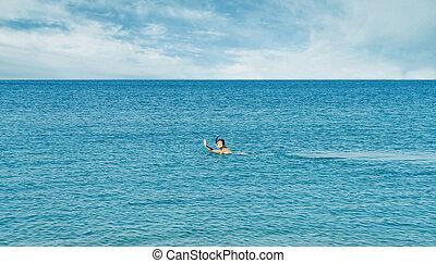 Girl snorkeling in mask in the sea