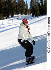 Girl snowboarding - A snowboarding young woman having fun on...