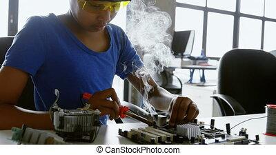 Girl soldering a circuit board at desk 4k